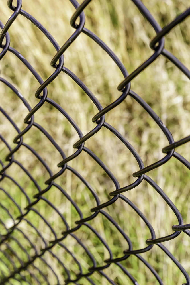 Receding pattern of chain-link fence (shallow depth of field), for themes of dependability, safety, protection, and transparency